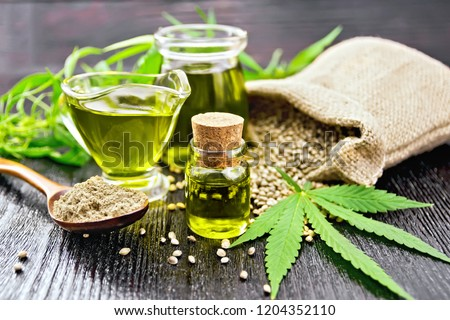 Hemp oil in two glass jars and sauceboat with grain in the bag, leaves and stalks of cannabis, a spoon with flour on the background of wooden boards #1204352110
