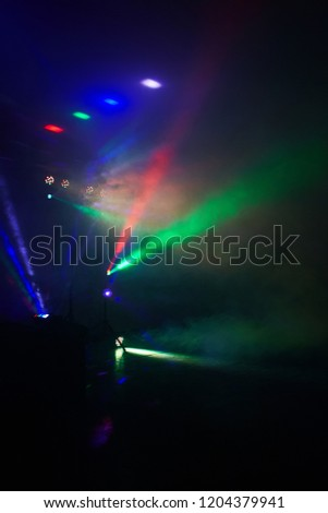 Stage lights in action at the concert. Lights show. Lazer show. Night club dj party people enjoy of music dancing sound with colorful light. club night light dj party club. Smoke Machine and lights #1204379941