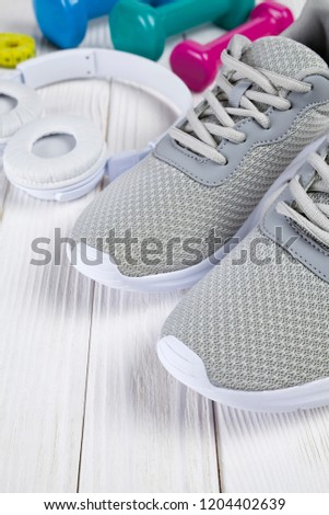 Gray sport shoes, white earphones, colored dumbbells and measuring tape on wooden table #1204402639