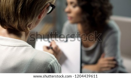 Sad lady telling psychotherapist about problems in her family, support and care Royalty-Free Stock Photo #1204439611
