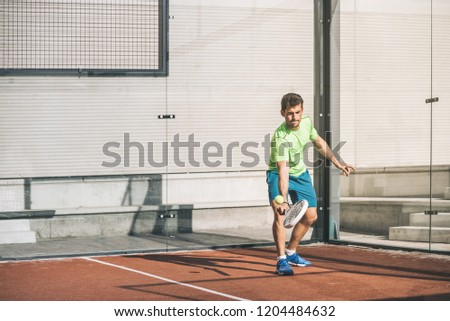 Man playing padel in a orange grass padel court outdoors behind the net #1204484632