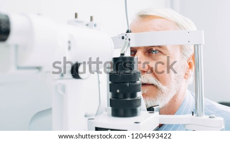 Senior patient checking vision with special eye equipment #1204493422