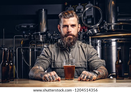 Portrait of a tattooed hipster male with stylish beard and hair in shirt sitting at the bar counter with glass of beer in indie brewery.   #1204514356