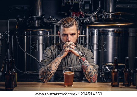 Portrait of a pensive tattooed hipster male with stylish beard and hair in the shirt in indie brewery.   #1204514359