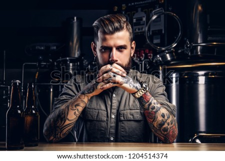 Portrait of a pensive tattooed hipster male with stylish beard and hair in the shirt in indie brewery.   #1204514374