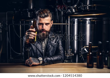 Stylish bearded biker dressed black leather jacket sitting at bar counter in indie brewery. #1204514380