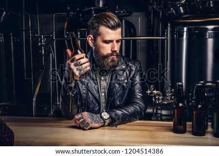 Stylish bearded biker dressed black leather jacket sitting at bar counter in indie brewery. #1204514386