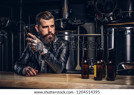 Stylish bearded biker dressed black leather jacket sitting at bar counter in indie brewery. #1204514395