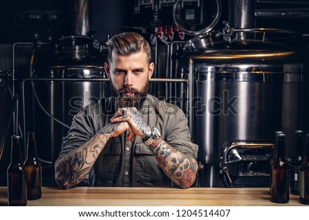 Portrait of a pensive tattooed hipster male with stylish beard and hair in the shirt in indie brewery.   #1204514407