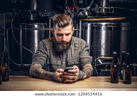 Tattooed hipster male with stylish beard and hair using smartphone while sitting at bar counter in the indie brewery.   #1204514416