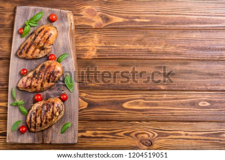 Grilled chicken breast ( fillet ) with basil and tomatoes . BBQ background #1204519051