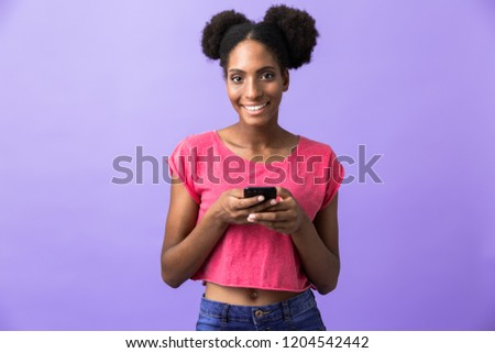 Photo of joyful african american woman smiling and holding mobile phone isolated over violet background #1204542442