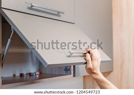 man hand open kitchen cupboard with handle, close up Royalty-Free Stock Photo #1204549723