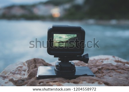 Small action camera shooting time-lapse on sunset.