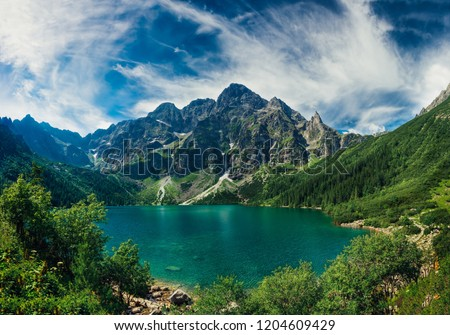 View on the turquoise color lake between high and rocky mountains. Beautiful alpine landscape.  #1204609429