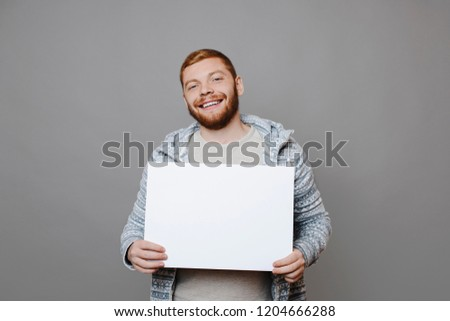 Handsome male in ginger beard smiling and looking at camera while standing on gray background and demonstrating blank banner #1204666288