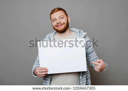 Handsome red-haired guy smiling and looking at camera while standing on red background and pointing at empty poster #1204667305