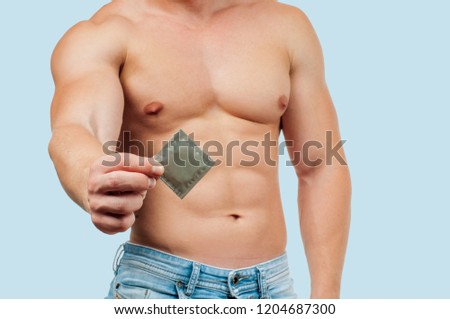 Safety sex concept. Handsome muscular man with condom on blue background  #1204687300