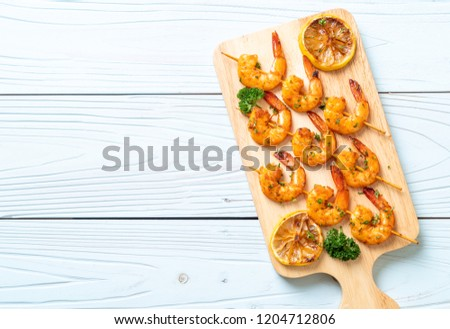 Grilled tiger shrimps skewers with lemon - seafood style #1204712806