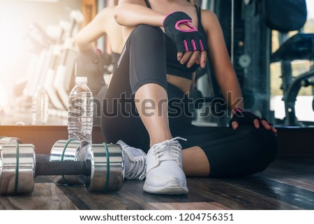 woman in black fitness suite sitting and breaking relax while exercise workout in gym #1204756351