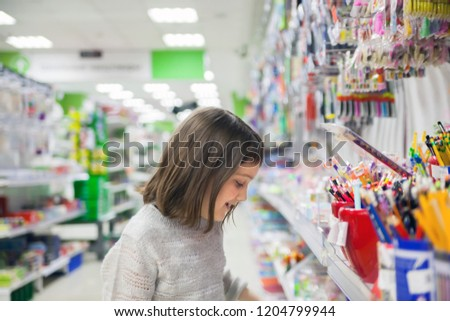 first grader buying pens and pencils in   bookstore  #1204799944