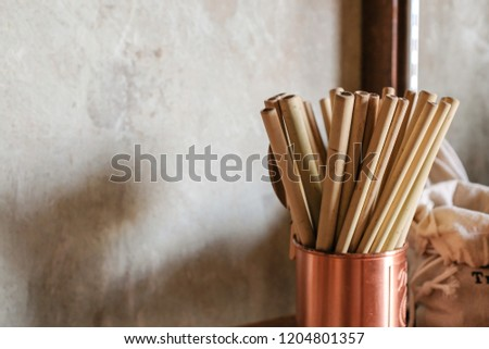Close up of natural color bamboo straws in rose gold bronze cup  with loft concrete background #1204801357