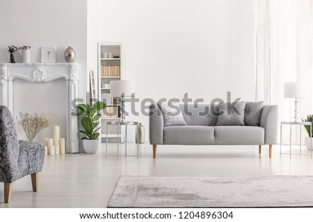 Lamp on table next to grey settee in white loft interior with armchair and copy space. Real photo #1204896304