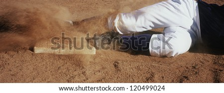 Motion blur low section show of a young baseball player sliding towards base on field Royalty-Free Stock Photo #120499024