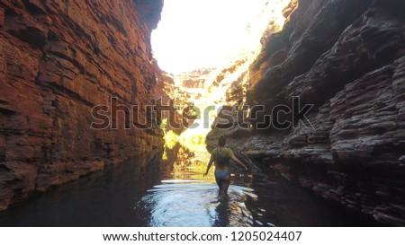 Tom Price, Australia - 09 10 2018: Young woman hiking through the Karijini National Park in Western Australia #1205024407