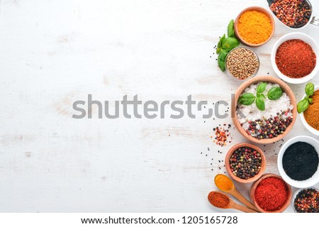 A set of Spices and herbs on a white wooden table. Basil, pepper, saffron, spices. Indian traditional cuisine. Top view. Free copy space. #1205165728