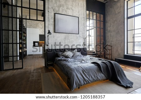 luxury studio apartment with a free layout in a loft style in dark colors. Stylish modern kitchen area with an island, cozy bedroom area with fireplace and personal gym #1205188357