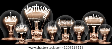 Photo of light bulbs with shining fibres in shapes of ADVERTISING concept related words isolated on black background #1205195116
