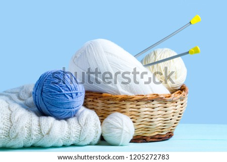 White and blue knitting yarn balls, knitting needles and a white knitted sweater on a blue background. Knitting concept. Knitted and winter clothes  #1205272783