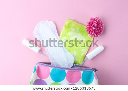 Tampons, feminine sanitary pads, flowers and women's cosmetic bag on a pink background. Hygiene care during critical days. Menstrual cycle. Caring for women's health. Monthly protection #1205313673