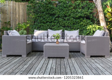 Large terrace patio with rattan garden furniture in the garden on wooden floor.