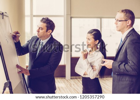Business expert drawing on flipchart for consulting two young colleagues. Business team discussing new project. Business meeting and brainstorming concept #1205357290