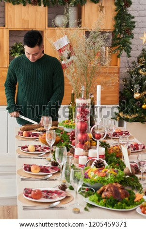 Young man in warm wool sweater cutting bread for Christmas dinner table #1205459371