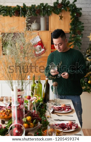 Handsome young Vietnamese man with wine glass standing at Christmas table #1205459374