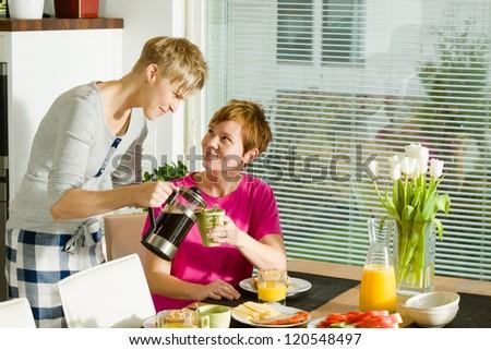 Happy lesbian couple on the breakfast table #120548497