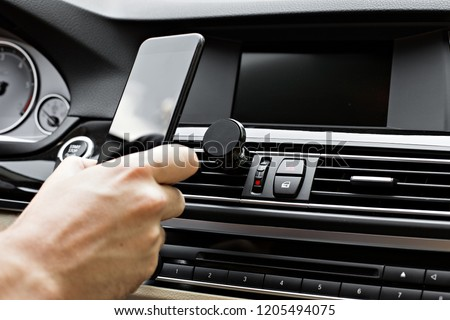 Mobile phone on magnet car mount phone holder for GPS. Lifestyles photo in car. Front view. With hand, phone. #1205494075