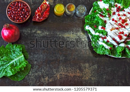 Healthy green salad with romaine lettuce, turkey breast, pomegranate and yoghurt sauce. Superfoods. Healthy eating concept. Keto lunch idea. Christmas salad with pomegranate and turkey. #1205579371