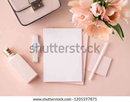 Flat lay scene in peach pink tones for self employed freelance girl. Feminine little things as a small bouquet, cosmetic bottle, bag and white watch. Sketch Pad or notebook mockup. #1205597875