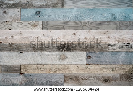 Pale faded brown and cool blue reclaimed wood surface with aged boards lined up. Wooden planks on a wall or floor with grain and texture. Neutral stained vintage wood background. #1205634424