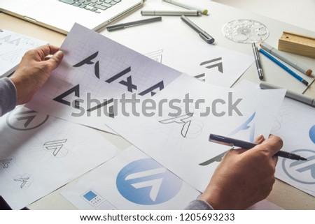 Graphic designer drawing sketch design creative Ideas draft Logo product trademark label brand artwork. Graphic designer studio Concept. #1205693233