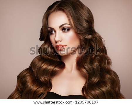 Brunette Girl with Long Healthy and Shiny Curly Hair. Care and Beauty. Beautiful Model Woman with Wavy Hairstyle. Make-Up and Black Dress #1205708197
