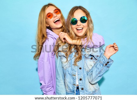 Two young beautiful blond smiling hipster girls in trendy summer clothes. Sexy carefree women posing near blue wall in sunglasses. Positive models going crazy #1205777071