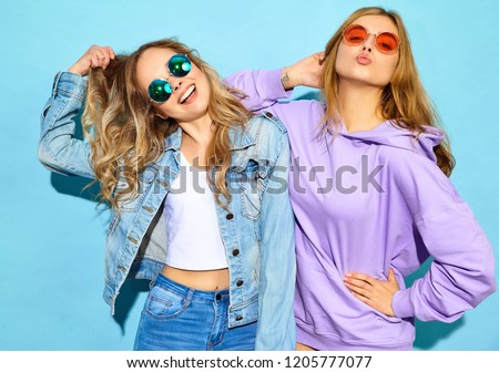 Two young beautiful blond smiling hipster girls in trendy summer clothes. Sexy carefree women posing near blue wall in sunglasses. Positive models going crazy #1205777077