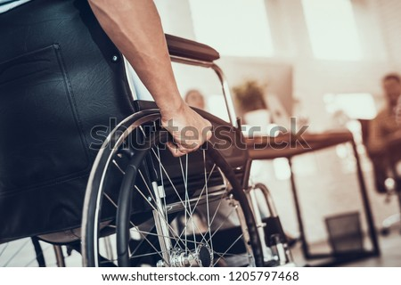 Close up. Disabled Man on Wheelchair in Office. Disabled Young Man. Man on Wheelchair. Recovery and Healthcare Concepts. Teamwork in Office. Young Workers. Sitting Man. Happy Worker. #1205797468