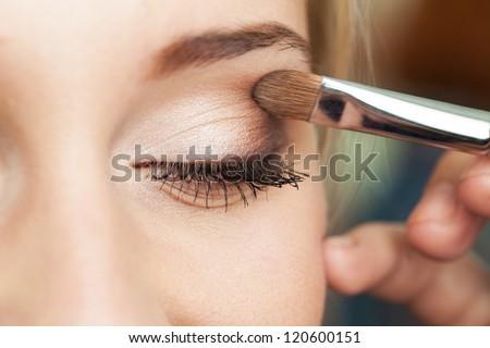 Eye makeup woman applying eyeshadow powder Royalty-Free Stock Photo #120600151