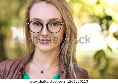 Portrait of young blonde woman with stylish glasses outdoor in park seeing the world with new eyes #1206080113
